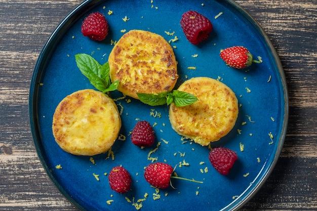 Cheesecakes com hortelã e framboesas vermelhas. sobremesa deliciosa, comida ucraniana. close up, vista de cima