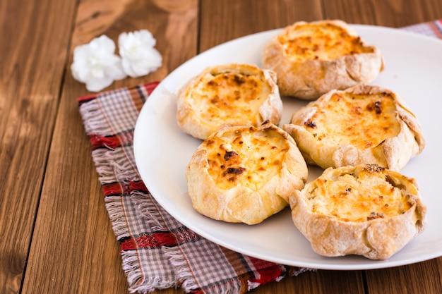 Cheesecakes com queijo cottage em um prato branco sobre uma mesa de madeira