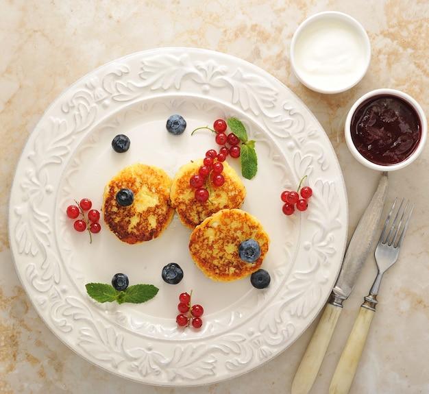 Cheesecakes com queijo cottage em um prato com creme de leite e geléia