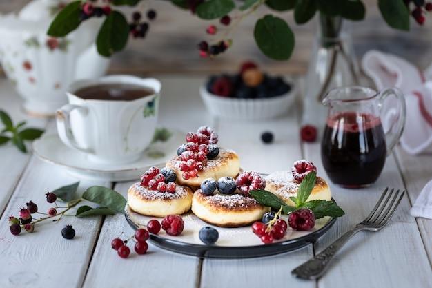 Cheesecakes de queijo cottage com frutas com um ramo de frutas irga.