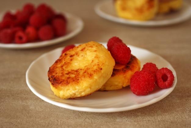 Cheesecakes redondos em um pires com framboesas frescas em um fundo bege claro