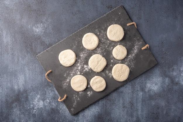 Cheesecakes semi-acabado em uma tábua de ardósia escura sobre um fundo de madeira