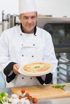 Chef alegre apresentando pizza