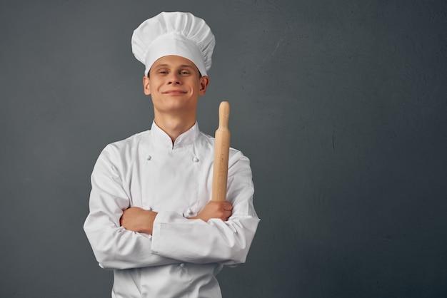 Chef alegre em itens de cozinha uniformes nas mãos de um restaurante profissional