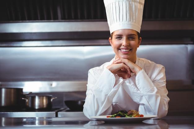 Chef, apoiando-se no balcão com um prato