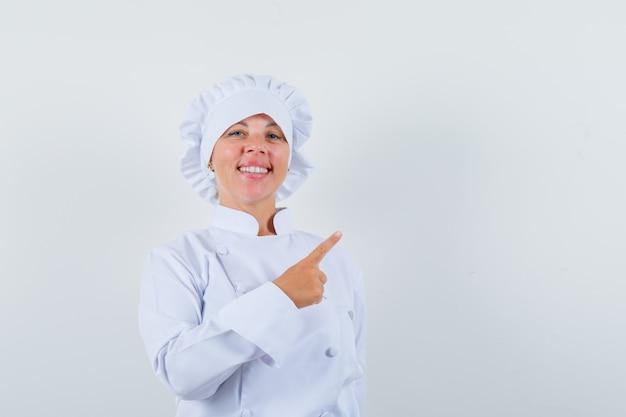 Chef apontando para o canto superior direito com uniforme branco e parecendo confiante