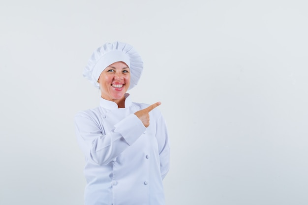Chef apontando para o lado em um uniforme branco e parecendo alegre