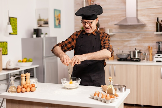 Chef aposentado quebrando ovos para farinha de trigo na cozinha de casa. chef de pastelaria idoso quebrando o ovo na tigela de vidro para receita de bolo na cozinha, misturando à mão, amassando.
