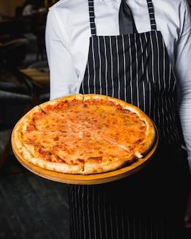 Chef apresenta pizza margherita na placa de madeira