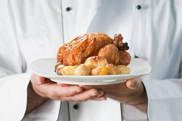 Chef apresentando e servindo frango assado com batatas