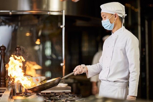 Chef asiático com máscara respiratória fazendo refogado em uma frigideira em chamas Foto Premium