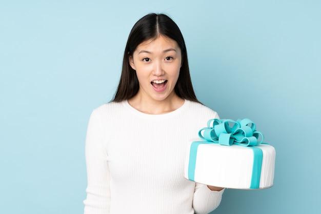 Chef asiático de confeitaria segurando um grande bolo isolado em um fundo azul com expressão facial surpresa e chocada
