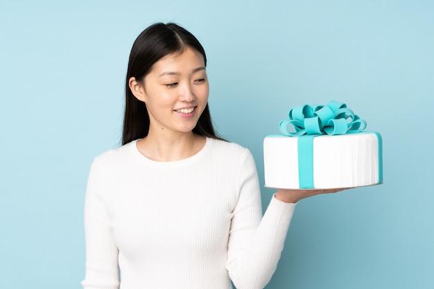 Chef asiático de pastelaria segurando um bolo grande na parede azul com expressão feliz