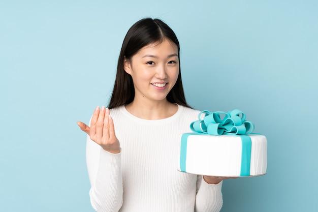 Chef asiático de pastelaria segurando um bolo grande na parede azul, convidando para vir com a mão