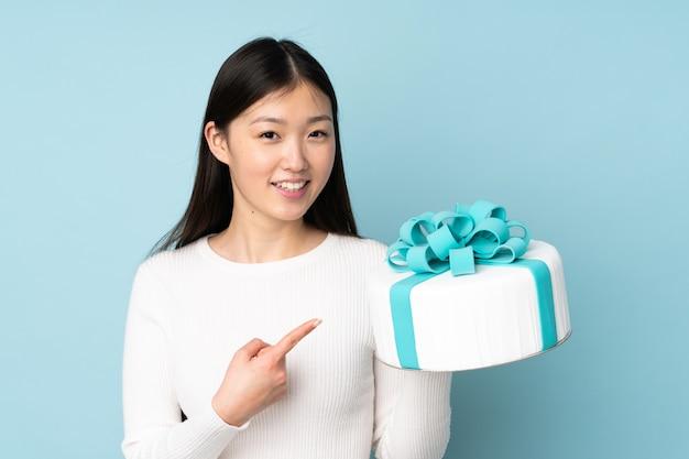 Chef asiático de pastelaria segurando um bolo grande na parede azul e apontando-o