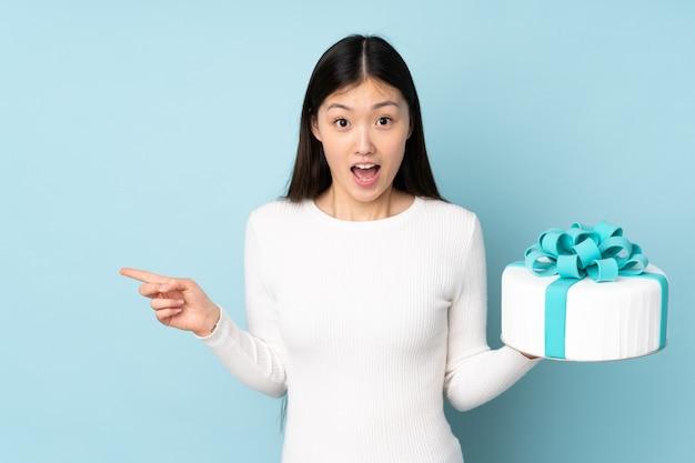 Chef asiático de pastelaria segurando um bolo grande na parede azul surpreendeu e apontando o dedo para o lado