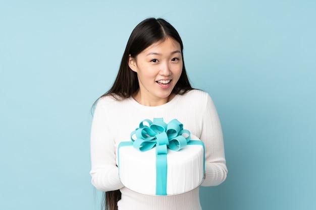 Chef asiático de pastelaria segurando um bolo grande na parede azul