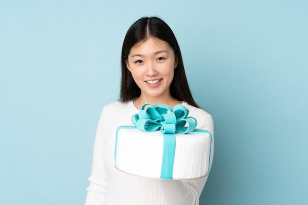 Chef asiático de pastelaria segurando um grande bolo isolado em um fundo azul com expressão feliz