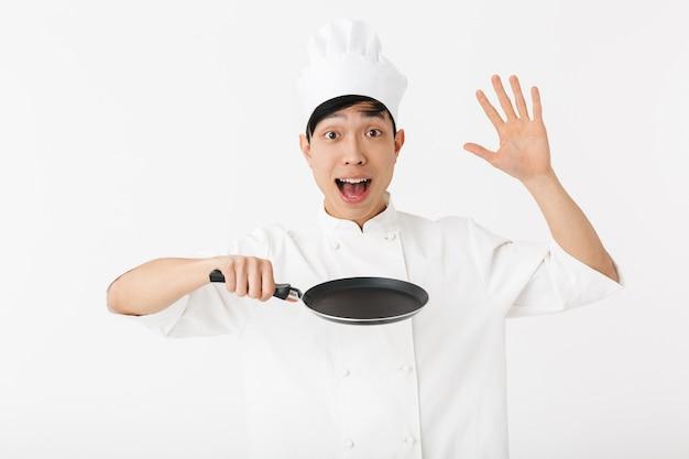 Chef asiático empolgado vestindo uniforme em pé, isolado na parede branca, mostrando a frigideira