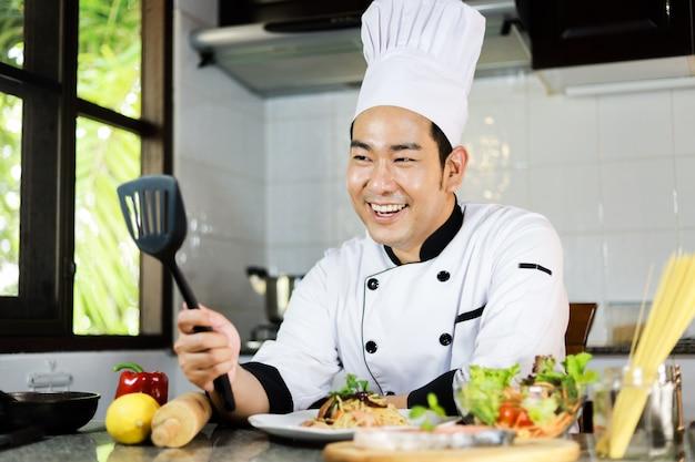 Chef asiático homem cozinhar alimentos no restaurante