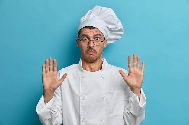Chef assustado levanta as mãos, mostra as palmas das mãos, diz que não sou culpado