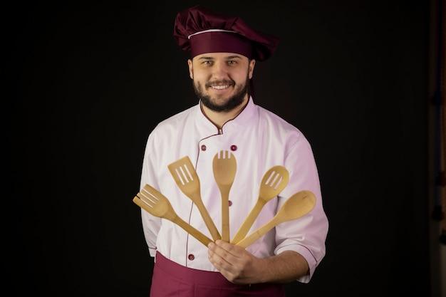 Chef barbudo bonito positivo homem de uniforme detém utencils de cozinha de madeira