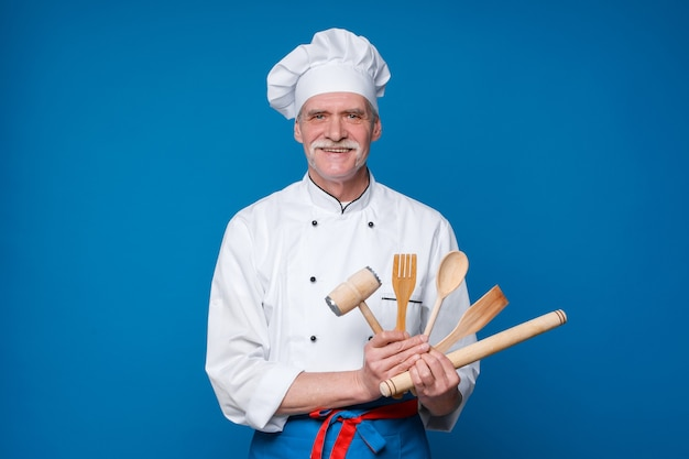 Chef barbudo com talheres em uniforme branco e chapéu na parede azul