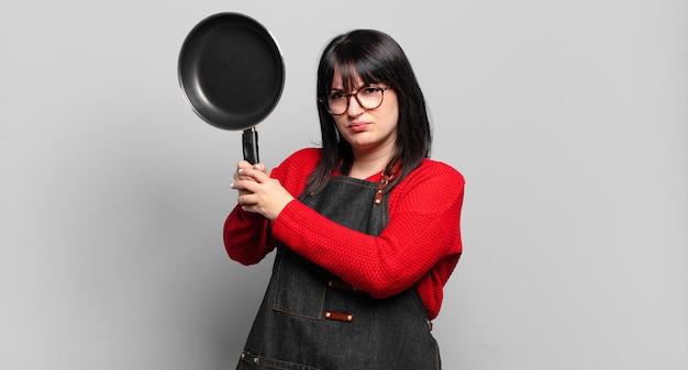 Chef bonita mulher de tamanho grande cozinhando com uma panela