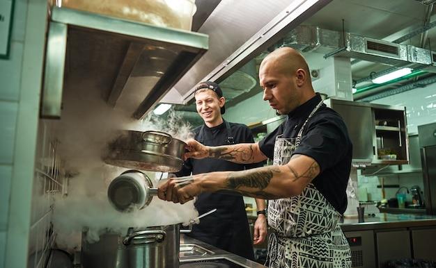 Chef bonito e confiante ensinando como cozinhar seus dois assistentes na cozinha de um restaurante