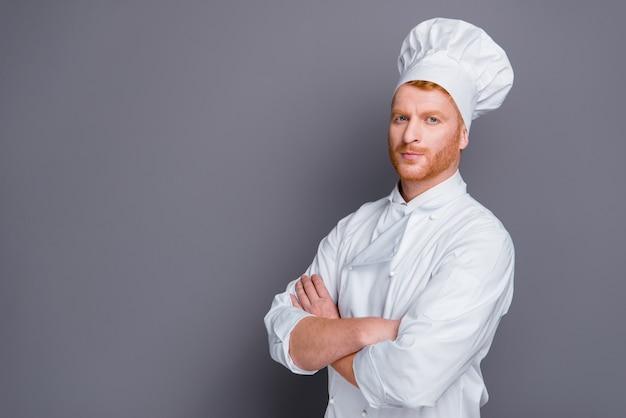 Chef bonito e ruivo posando contra a parede cinza