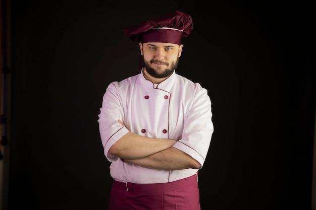 Chef bonito homem de uniforme fica com os braços cruzados olha para a câmera