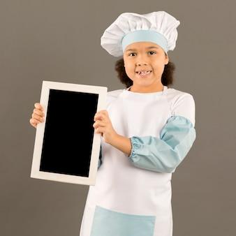 Chef bonito segurando o quadro em branco