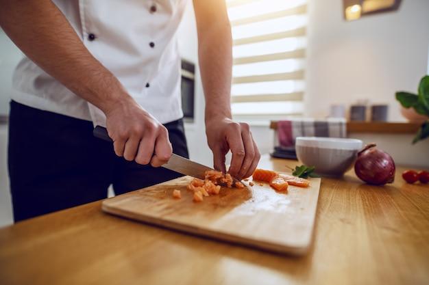 Chef caucasiano dedicado de salmão picado uniforme em pedaços pequenos.