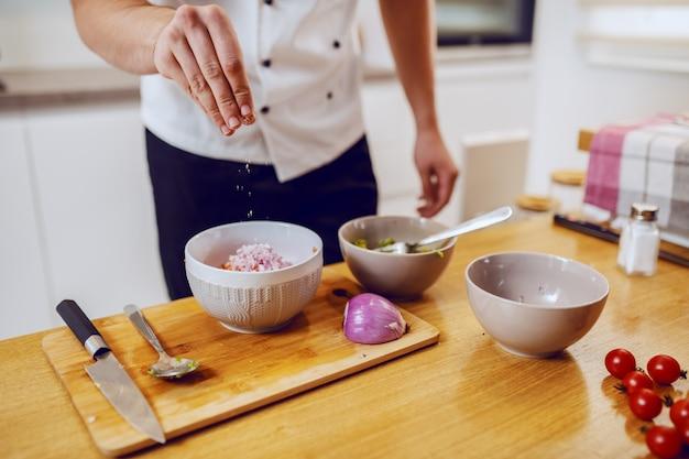 Chef caucasiano dedicado em uniforme permanente na cozinha e adicionando sal em uma tigela com legumes.