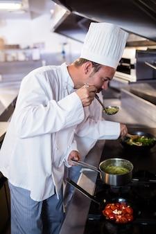 Chef cheirando comida na cozinha