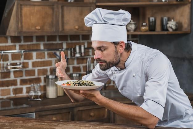 Chef, cheirando o aroma do prato na cozinha