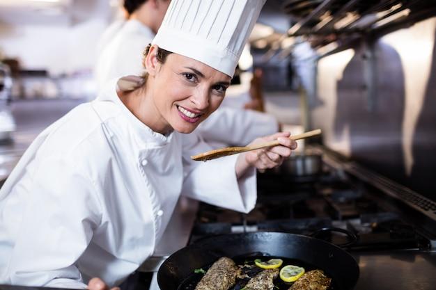 Chef cheirando peixe frito na cozinha