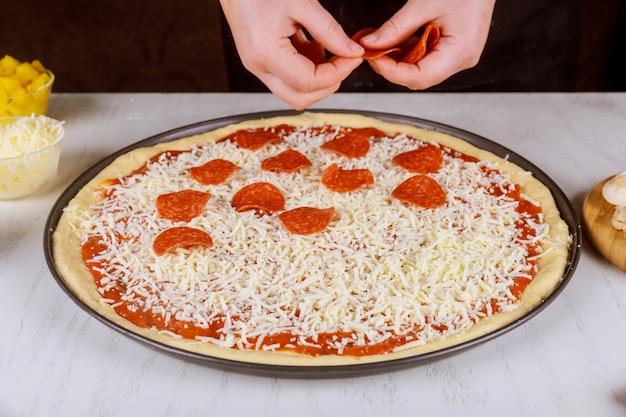 Chef coloca calabresa na massa de pizza crua.