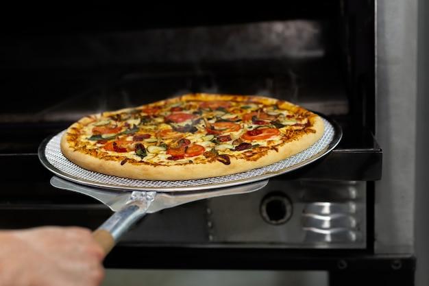 Chef, colocando a assadeira de pizza no forno no restaurante com equipamento de pá de pizza.