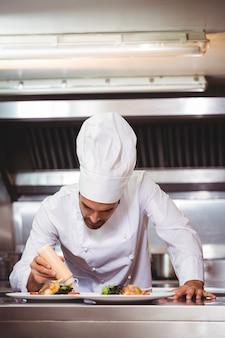 Chef, colocando o molho em um prato