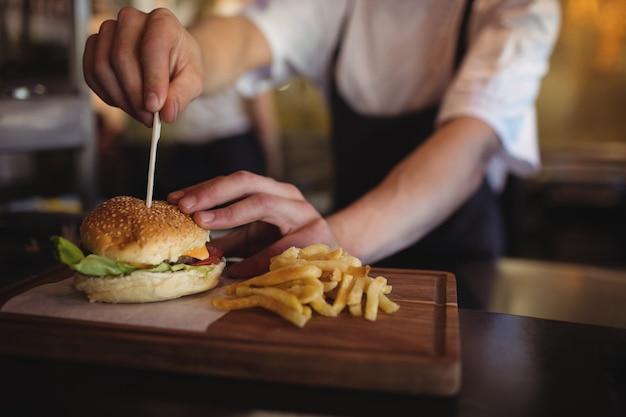 Chef colocando palito sobre o hambúrguer na estação de pedidos