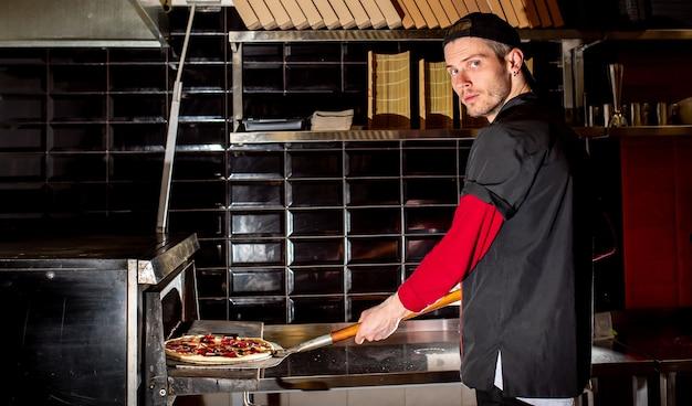 Chef colocando pizza no forno para cozinhar