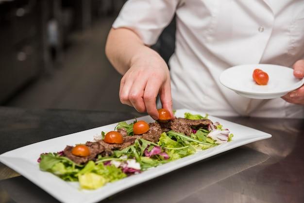 Chef, colocando tomates frescos na salada