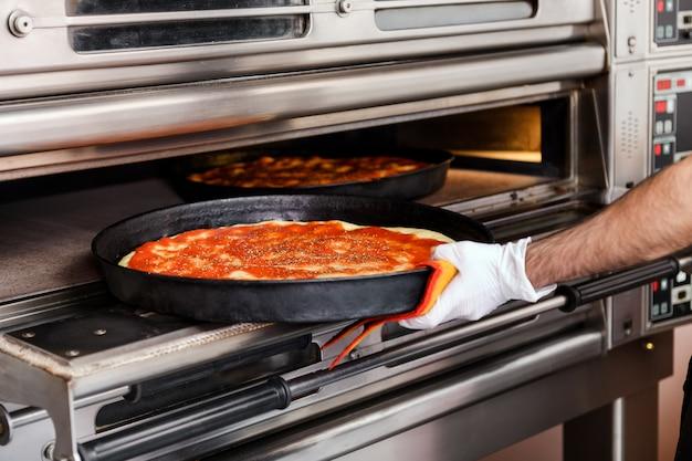 Chef, colocando uma pizza em uma bandeja no forno