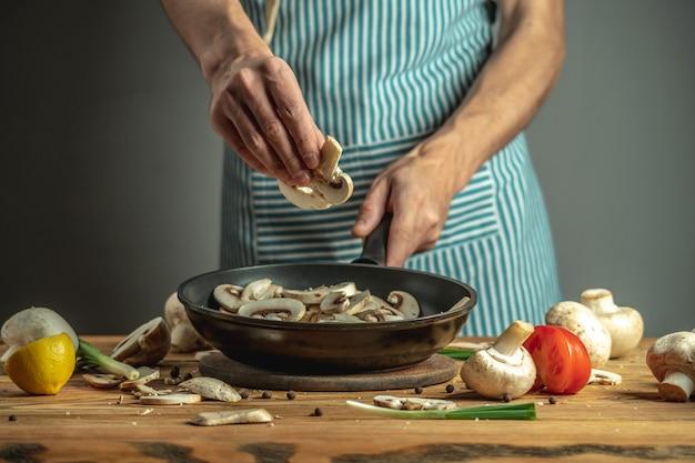 Chef coloque cogumelos frescos fatiados em uma frigideira. conceito do processo de cozimento de alimentos.
