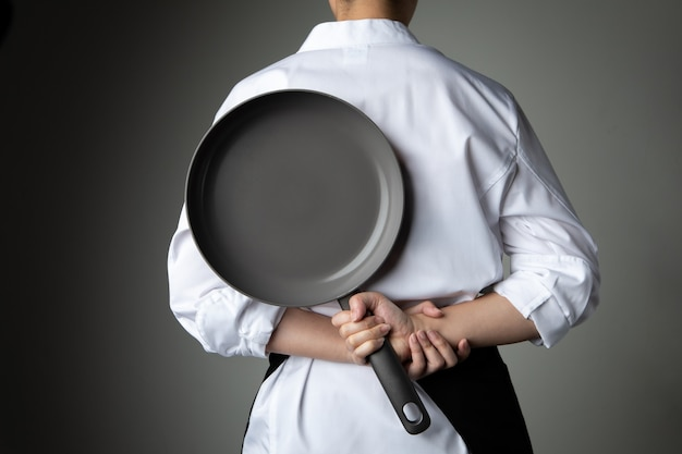 Chef com a mão segura a panela em fundo cinza