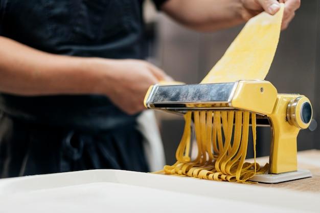 Chef com avental usando máquina para fatiar massa
