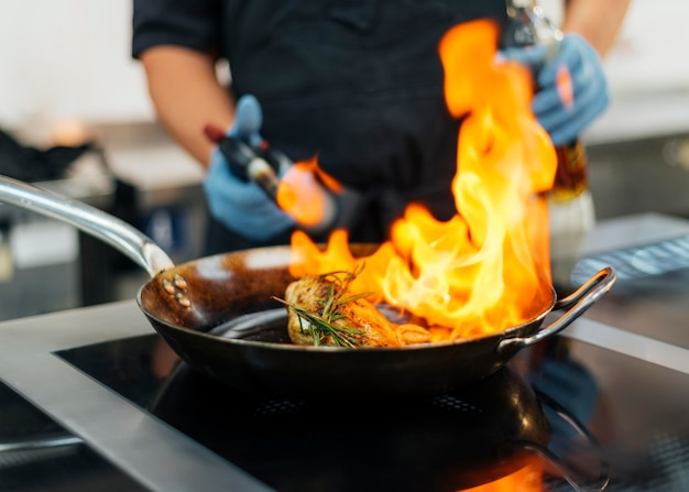 Chef com luvas de flambar prato