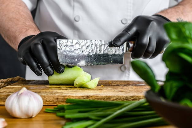 Chef com luvas pretas cortando um pepino verde fresco em uma tábua de madeira