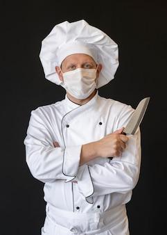 Chef com máscara médica segurando uma faca